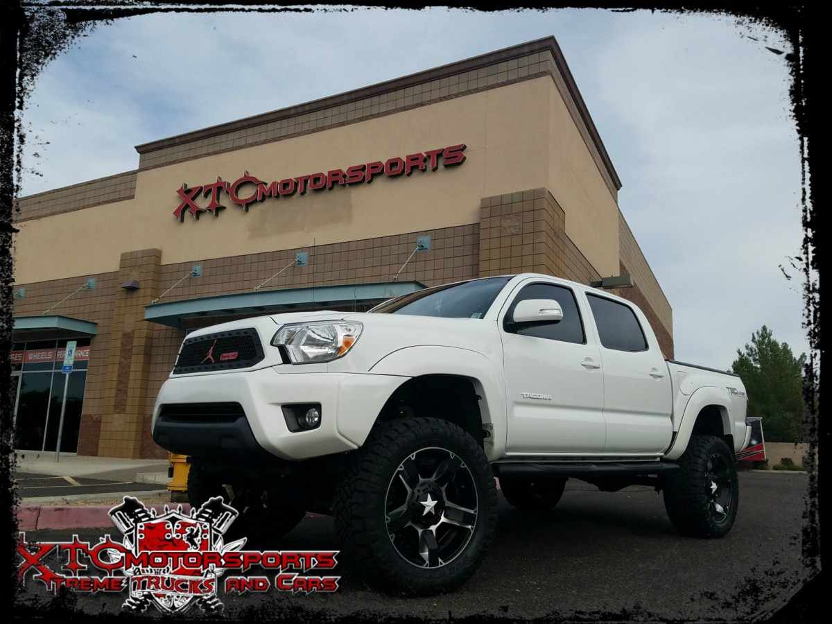 """Tessa Powell brought us her 2014 Toyota USA Tacoma for a 6"""" BDS Suspension lift with BDS NX2 Series Nitro shocks, and it is standing on some 33x12.50R20 Nitto Tire Ridge Grappler tires wrapped around some XD wheels Rockstar 2 Matte Black & machined wheels with a White Star."""